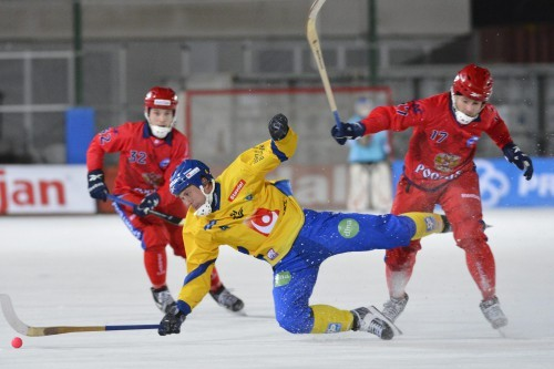 Sweden's Hellmyrs falls in front of Russia's Bulatov and Saveliev during their Bandy World Championship match in Goteborg