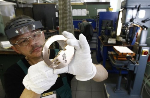 An employee works on a silver medal for the 2014 Winter Olympic Games in Sochi, at the Adamas jewellery factory in Moscow