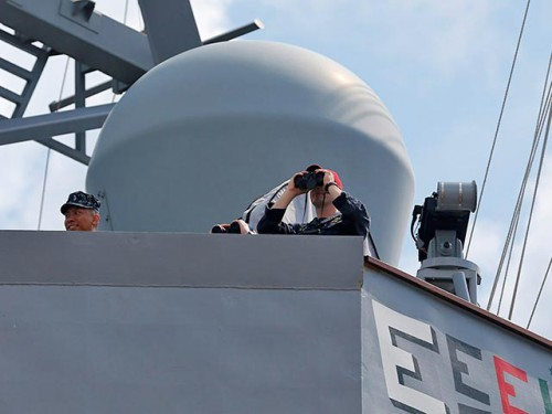 Crew members look through binoculars on the destroyer USS Donald Cook in the Black Sea port of Constanta