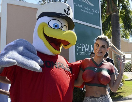 A fan wears a bird costume with the name of Cristiano Ronaldo on the chest while posing for other fans with Andressa Urach in Campinas