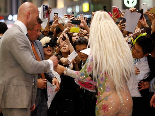 Fans of singer Lady Gaga take pictures upon her arrival at Narita international airport