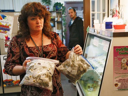 Cheri Hackett, co-owner of BotanaCare, carries bags of the company's sample packs of marijuana in Northglenn, Colorado