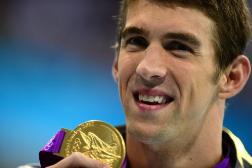 US swimmer Michael Phelps shows off his gold medal after the podium ceremony for the men's 200m individual medley swimming event at the London 2012 Olympic Games on August 2, 2012 in London. AFP PHOTO / MARTIN BUREAU (Photo credit should read MARTIN BUREAU/AFP/GettyImages)